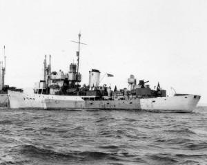 "TRENTONIAN anchored outside of Cherbourg, France in her ""false hull"" camouflage scheme, September 1944.  The maple leaf on her funnel is visible and her name board has been hung on the railings above the depth charge throwers.  Her pennant number has been partially removed by censors.  Roger Litwiller Collection, Allen B. Singleton, RCNVR photo, courtesy Dougals Campbell, RCNVR. (RTL-DC041)"