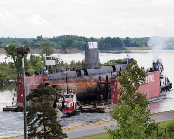 HMCS OJIBWA is towed through the Iroquois Lock on 3 June 2012, to start her next career. The decommissioned Canadian submarine from the Cold War will be refitted and rest at Port Burwell, Ontario as a museum and memorial to the Canadian men and women who fought the Cold War.  This photo was Published in Action Stations Magazine, Summer 2012, Vol 30 Issue 4, pg 15. Roger Litwiller Collection, courtesy Roger litwiller. (RTL33818)