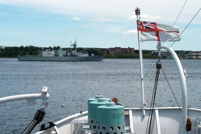 HMCS CHARLOTTETOWN a modern Canadian frigate, passes the stern of HMCS SACKVILLE, a WWII corvette on 7 July 2007. SACKVILLE is the last remaining flower class corvette in the world and is now a proud memorial to Canada's sailors in Halifax. I highly recommend a visit to this amazing ship to learn more about our veterans and how they served.  Roger Litwiller Collection, photo courtesy Roger Litwiller. (RTL100_1645)