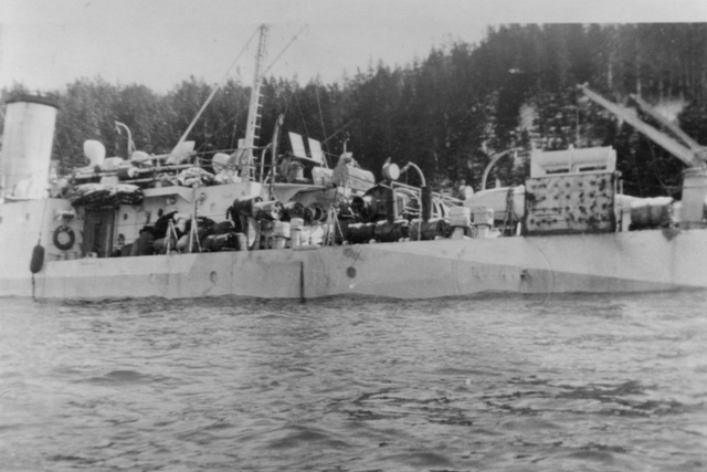 HMCS QUINTE, Bangor class minesweeper, had grounded on Horse Head Shoal on 30 Novemeber 1942.  She quickly began to take on water and was beached near St. Peter's, Cape Breton. Salvage operations on QUINTE were begun by the Foundation Maritime Ltd's ship Foundation Aranmore.  She was re-floated ten days later and moved to the wall at St. Peter's Canal to continue pumping operations  Unfortunately for QUINTE her ordeal was not yet over, she capsized in St. Peters Canal during salvage operations.  QUINTE has the dubious distinction of being the only Royal Canadian Navy ship to sink twice in ten days.  Discover the remarkable story of HMCS QUINTE in Warships of the Bay of Quinte.  Roger Litwiller Collection -Photo Courtesy Walter Gregory. (RTL-WG005)