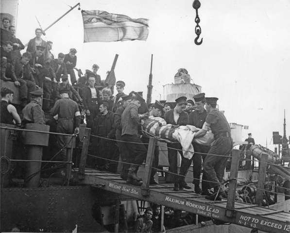 A critically wounded sailor from HMTS MONARCH is carried ashore from HMCS TRENTONIAN on 13 June, 1944 in Portsmouth.  Roger Litwiller Collection, courtesy Douglas Campbell, RCNVR. (RTL-DC004)