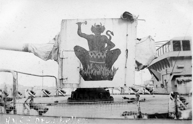 HMCS DRUMHELLER's gunshield art as designed by her ships company.  Painted on the corvettes forward 4 inch gun, it depicts the devil beating on a fiery drum.  The photo was taken in St. John's NF in 1943.  Roger Litwiller Collection, courtesy Ross Milligan, RCNR. (RTL-REM173)