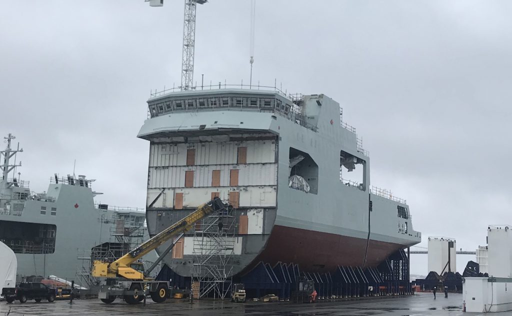Construction of the Arctic and Offshore Patrol Vessel, future HMCS MARGARET BROOK is progressing well as the middle and stern sections are rolled out of the Irving Shipyard's assembly building in September 2018. Photo courtesy of Halifax Shipping News.