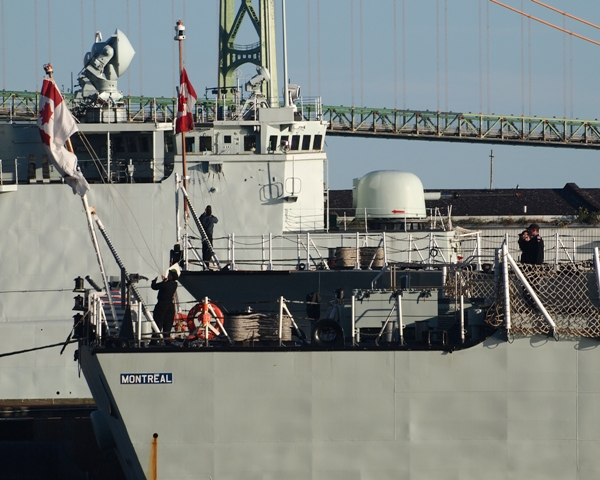 HMCShips MONTREAL and CHARLOTTETOWN raise the RCN Ensign and Jack during morning Colours while at HMC Dockyard, Halifax on 5 September 2015. Decommissioned RCN destroyer, HMCS IROQUOIS is in the background. Roger Litwiller collection, courtesy Roger Litwiller. (RTL53627)